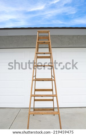 A tall wooden step ladder is positioned in from of a home's garage for a home inspector to view the roof. Composed so the sky can be used for placement of copy. - stock photo