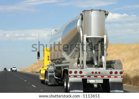 A tanker truck transports some type of liquid to who knows where. - stock photo