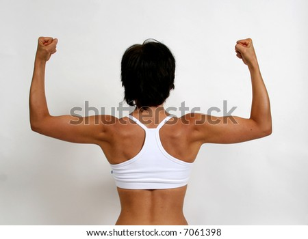A tanned woman flexing her arm muscles - stock photo