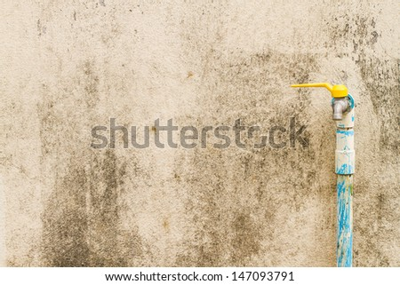 A tap and tube on rusty background