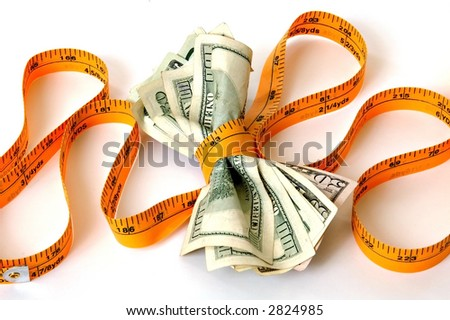 a tape measure pulled tightly around money - stock photo