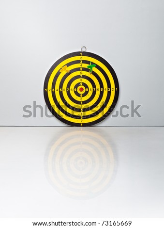 A target with a darts on on a grey background