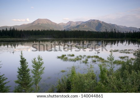 A tarn or lake just off Highway 2 reflects the Alaska mountain landscape