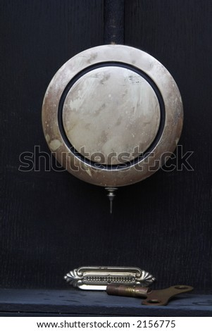 A tarnished silver antique clock pendulum, level gauge, and winding key viewed in wooden clock case - stock photo
