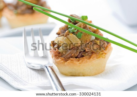 A tartlet appetizer filled with mushrooms and foie - stock photo