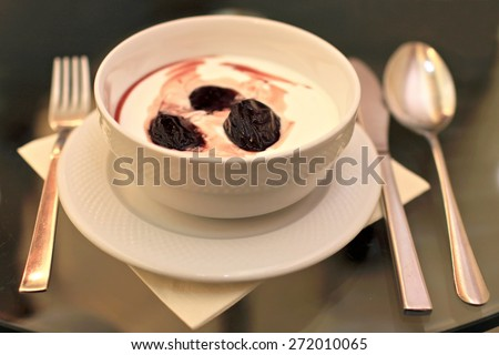 A tasteful bowl of yogurt with prune