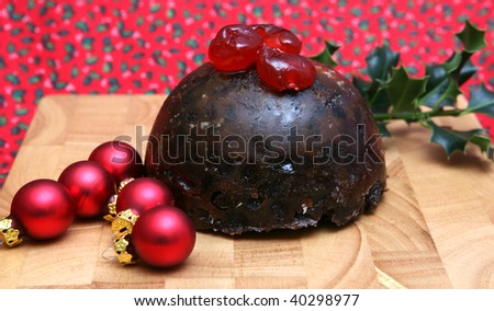 A tasty Christmas Pudding with Cherries Holly and Baubles - stock photo