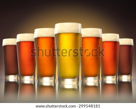 A tasty delicious row of a variety craft brew tap beers in pub glasses on reflective surface - stock photo