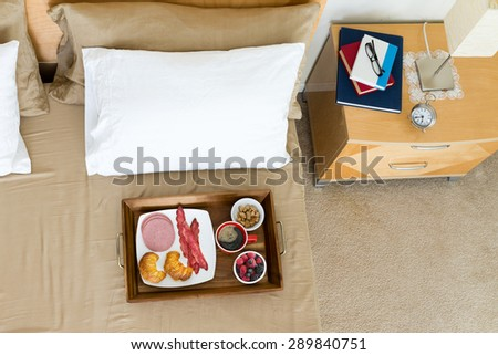 A tasty healthy breakfast in bed with coffee, fresh berries, bacon and croissants alongside a bedside cabinet with reading books for a relaxing weekend lie in bed - stock photo