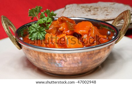 A tasty meal of Chicken Curry served in a Balti dish or Karahi, with chapattis - stock photo