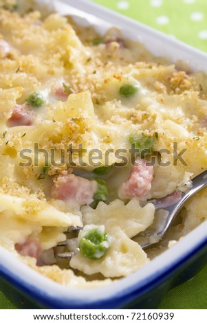 A tasty variation of macaroni and cheese - Diced ham, green peas, and bowtie pasta baked in a rich, creamy, cheese sauce. - stock photo