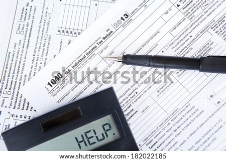 A tax form, pen and calculator - stock photo