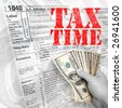 A tax time themed montage for US taxpayers with a hand full of money fanned out. - stock photo