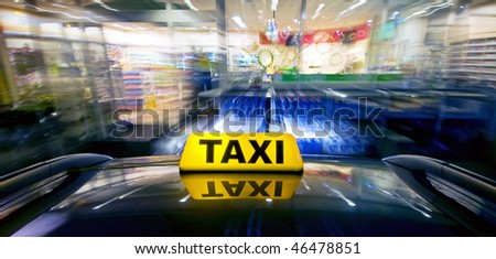 A taxi at high speed closing in on a night shop for a ram raid - stock photo