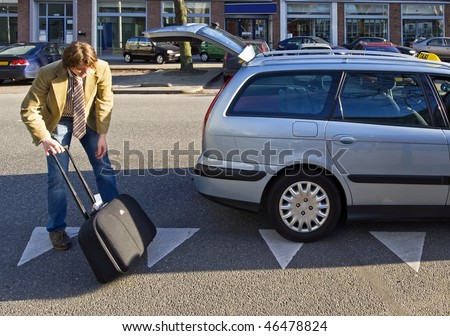 A taxi driver putting luggage in the trunk of his cab. - stock photo