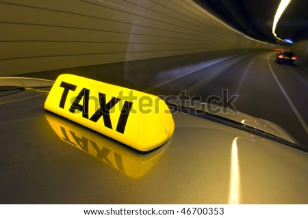 A taxi, racing through a tunnel overtaking cars - stock photo