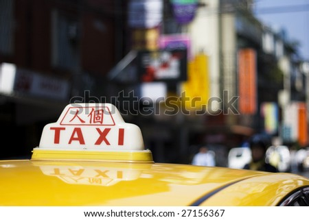 A taxi sign with the Chinese characters 'ren ge', which means 'freelance driver'.  It's a city scene but shallow depth of field has reduced the signs to a blur of color and patterns.