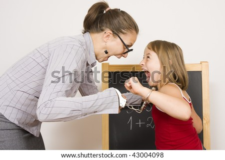 A teacher and a little schoolgirl screaming to each-other, bound with handcuffs together. - stock photo