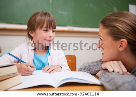 A teacher and a schoolgirl talking in a classroom - stock photo