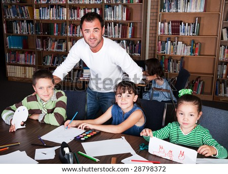 A teacher guides his students in an art class in the school library. - stock photo