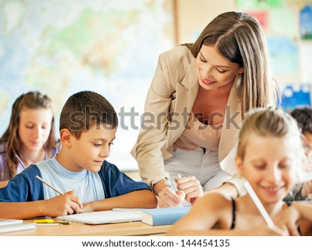 A teacher helping one of her students in class. - stock photo
