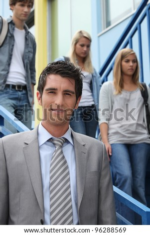 A teacher looking at us and three students in the background. - stock photo