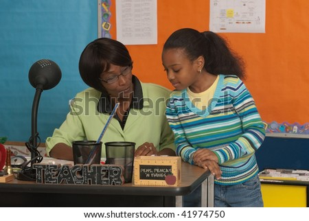 A teacher reviews a students work - stock photo
