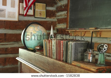 A teacher's desk and a chalkboard in an old-fashioned one-room schoolhouse. - stock photo
