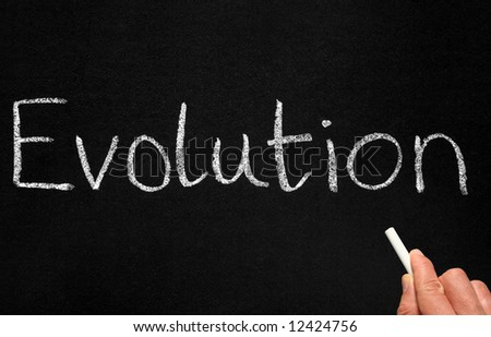 A teacher writing evolution on a blackboard. - stock photo