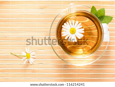 A teacup  with herbal chamomile tea and flower - stock photo