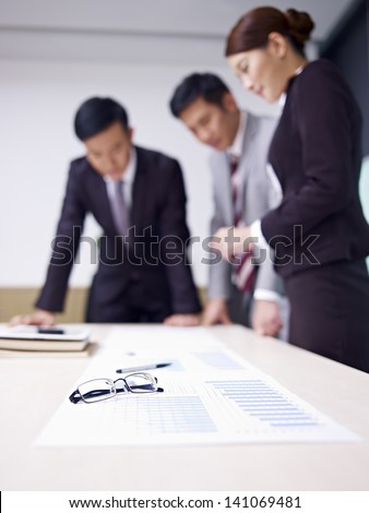 a team of asian business people working together in office, focus on glasses. - stock photo