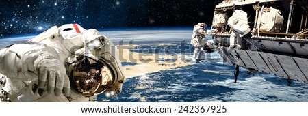A team of astronauts perform work on a space station while orbiting a large, Earth-like planet. The stars of the galactic core radiate in the background. Elements of this Image Furnished by NASA. - stock photo