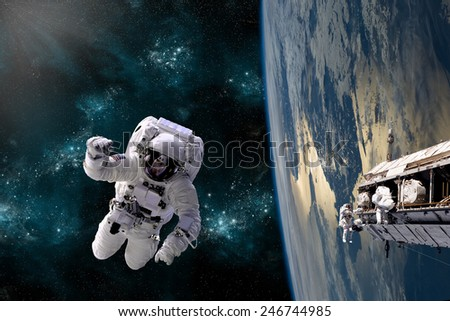 A team of astronauts perform work on a space station while orbiting Earth. The Baltic regions appear below. Elements of this Image Furnished by NASA. - stock photo