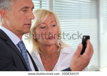 A team of business professionals reading a text message - stock photo