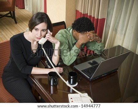 A team of businesspeople receive bad news while working late in a hotel room on a business trip. - stock photo