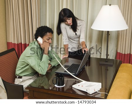 A team of businesspeople review results on a laptop while working late in a hotel room on a business trip. - stock photo