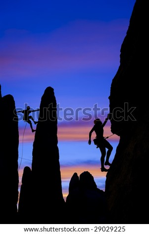 A team of climber is silhouetted against the evening sky as they ascend a steep rock face in Joshua Tree National Park, California. - stock photo