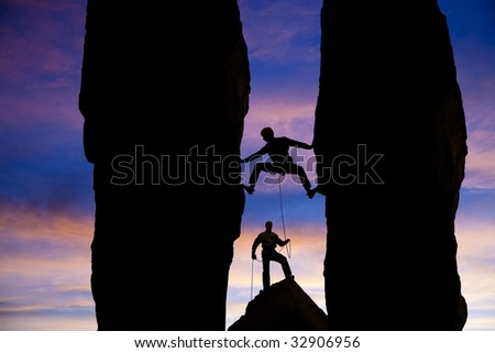 A team of climbers are silhouetted as they work their way up a gap between two pinnacles in the Sierra Nevada  Mountains, California. - stock photo