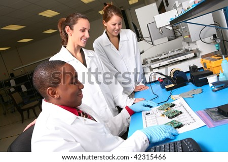 A team of computer technicians working on computer parts in the lab - stock photo