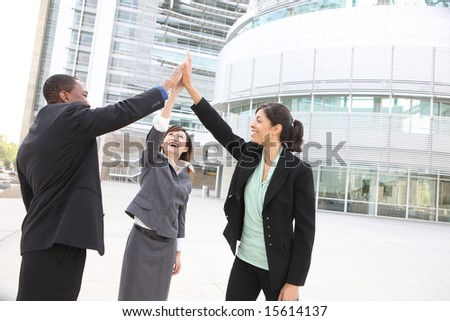 A team of diverse business people at office building celebrating success - stock photo