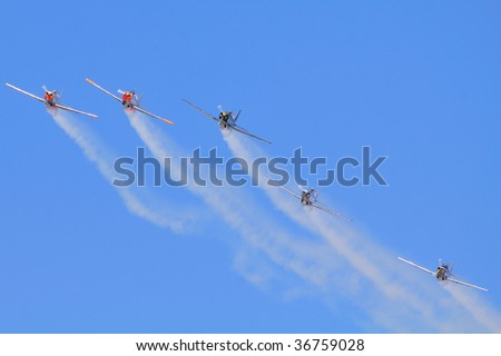 A team of five small single engine propeller aircrafts flying in close formation