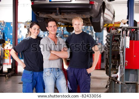A team of mechanics in a shop with a car on a hoist - stock photo