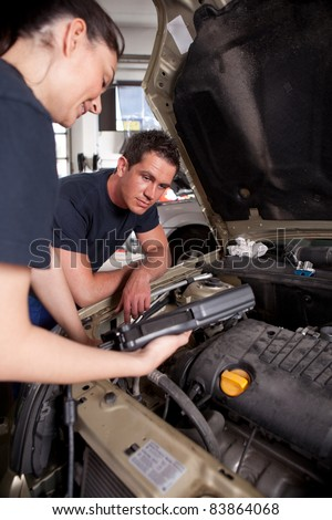 A team of mechanics using an electronic diagnostics tool - stock photo