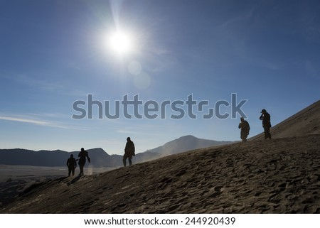 A team of military uniform people walking down side of crater  - stock photo