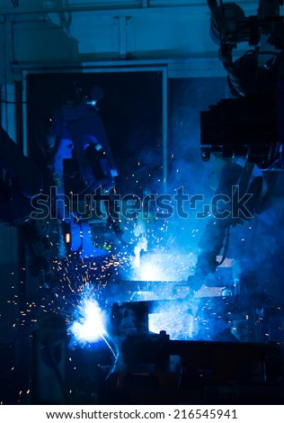 A team of robots welding in automobile parts industry. - stock photo
