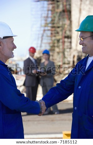 A team of shipping engineers in front of an oil platform in the harbor, with two shaking hands in the foreground - stock photo