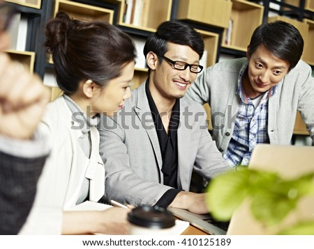 a team of young asian business people working together using laptop computer, happy and smiling. - stock photo