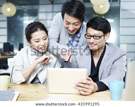 a team of young asian entrepreneurs discussing business in office using tablet computer. - stock photo