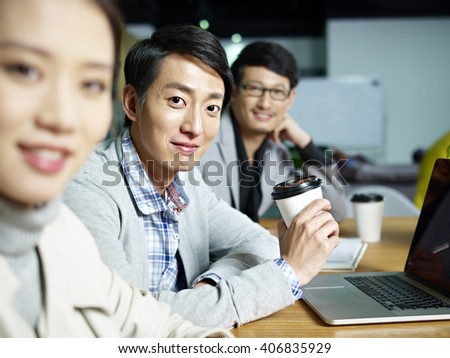 a team of young asian entrepreneurs posing in meeting room, focus on the young man in middle.
