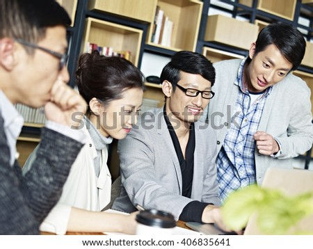 a team of young asian entrepreneurs working together using laptop computer in office. - stock photo